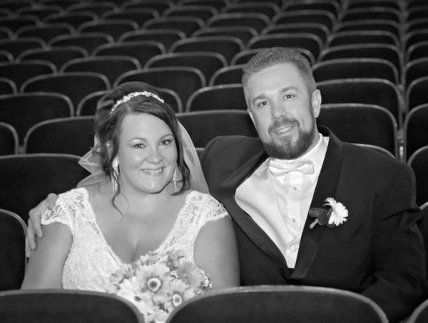 Bride and groom photograph in black and white of them sitting in the seats at the Riviera Theater