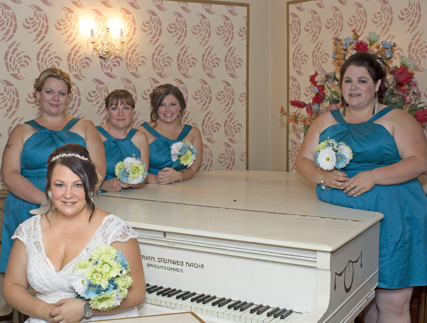 The bride and bridesmaids around a grand piano
