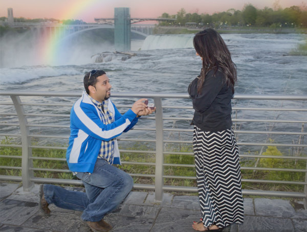 Handsome young Indian man proposing to his future wife with Niagara Falls in the background with rainbow overhead