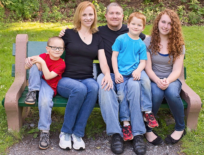 Lovely family sitting on a park bench at a nature trail