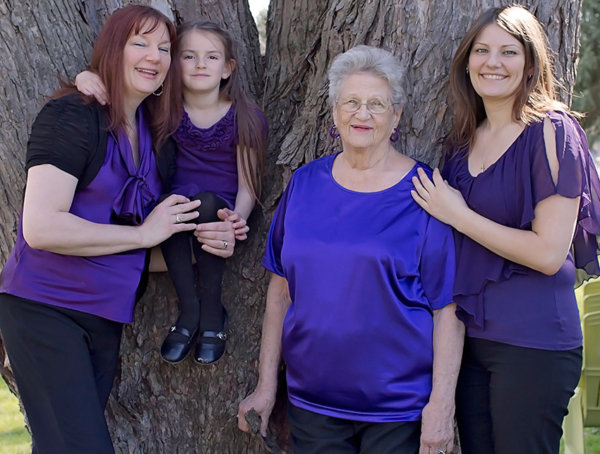 Generational photograph of four generations of women dressed in matching purple blouses.