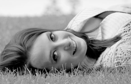 Closeup of a beautiful young woman in the grass from Senior Photo Session