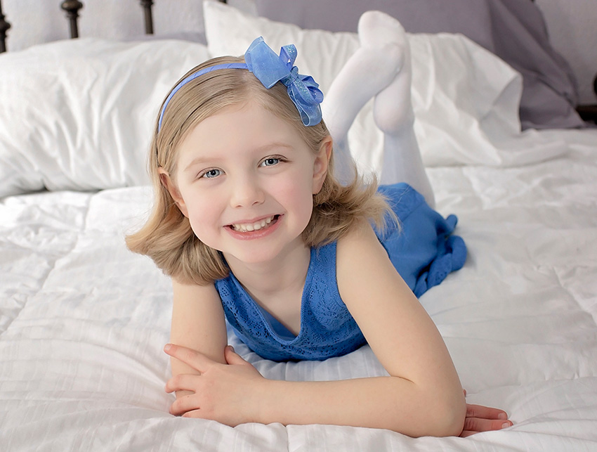 Happy little girl in a pretty dress and blue bow posing in this portrait at her home