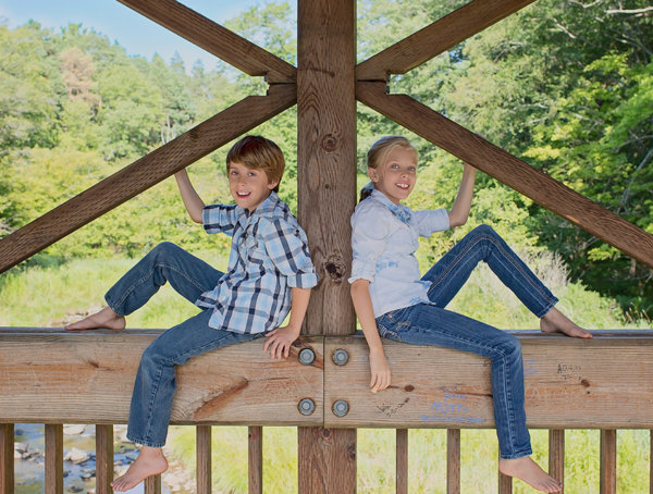 Young brother and sister posing on a rustic bridge over a stream in Allegany State Park