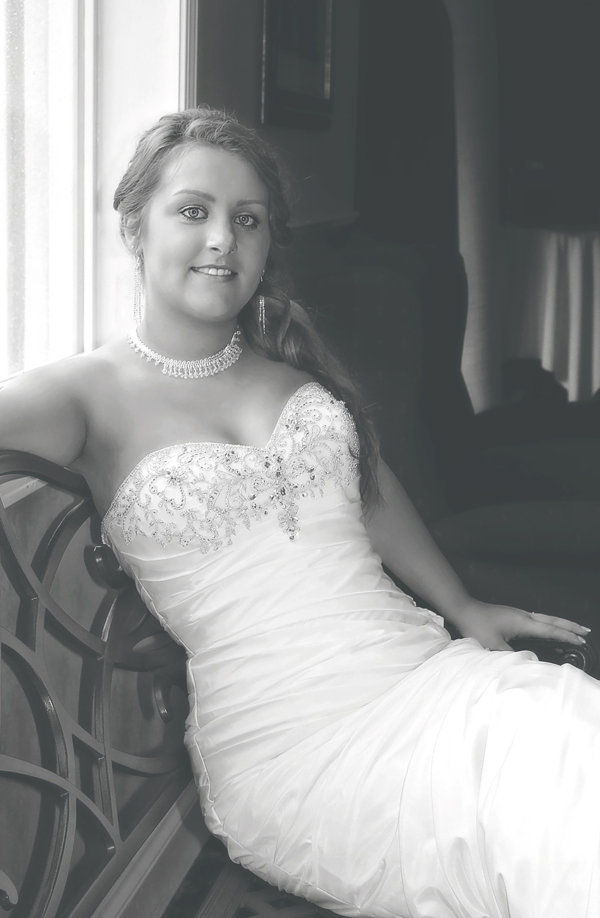 Black and white photograph of a beautiful bride sitting before her wedding ceremony in her wedding gown.