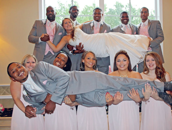 Bride and groom being lifted up by their wedding party