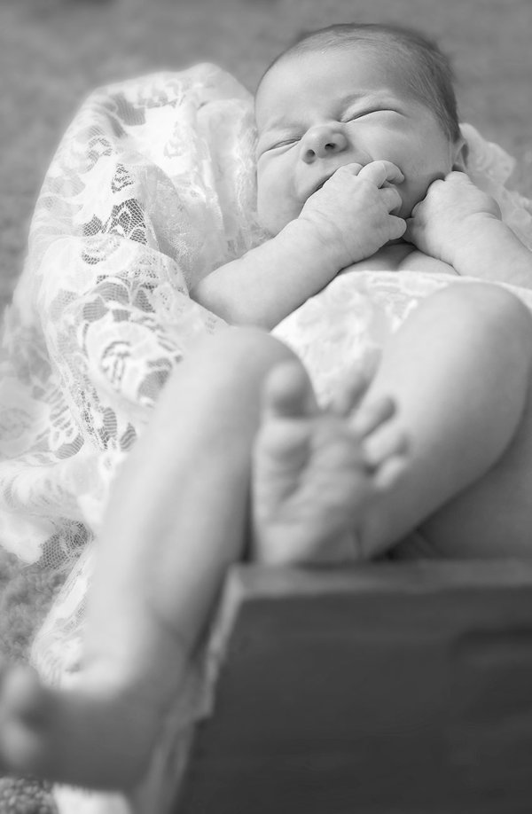 Black and white photo of a newborn infant boy with feet hanging out with lace lining of a wooden basket