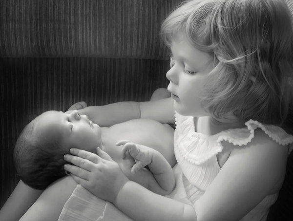 Newborn photography of baby boy and his big sister (toddler) holding him in her lap