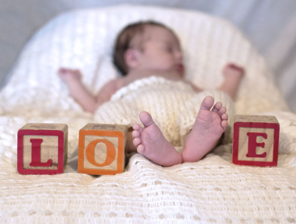 Newborn photo that spells out love with the baby's feet and wooden play blocks