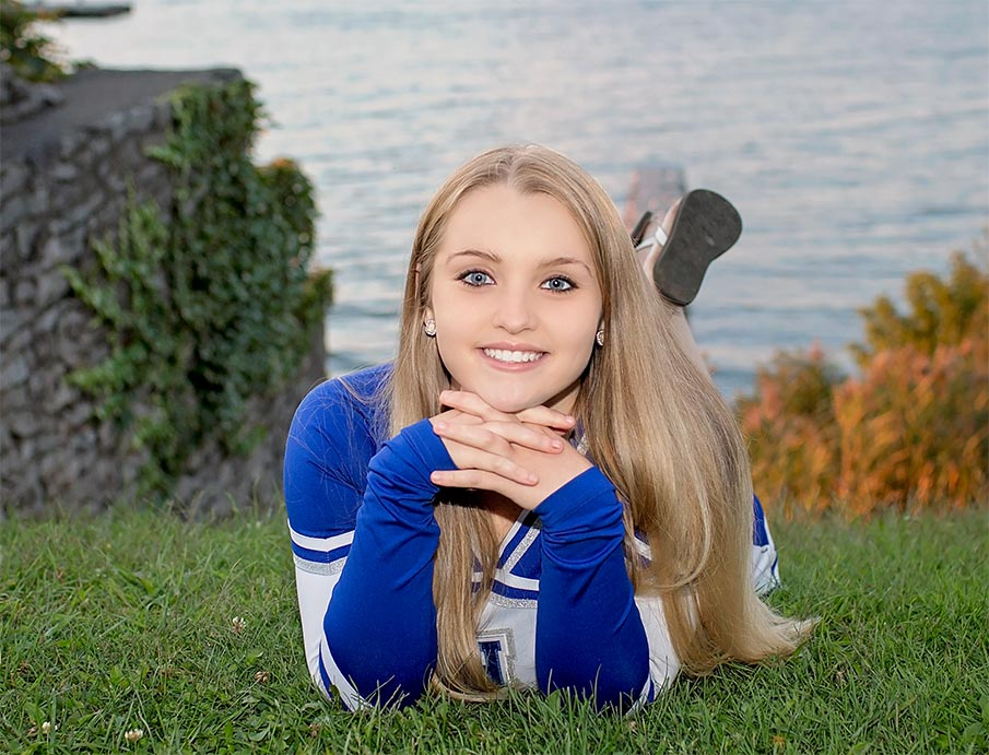 young woman posing in her blue cheerleader uniform for a senior picture by Lake Ontario