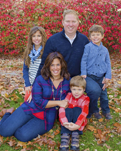 Smiling Family posing for family photography portrait on a colorful fall day.