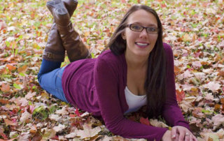 High school senior during laying in fall leaves during photo session.