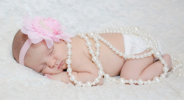 Baby photographer newborn baby girl with pink flower and pearls